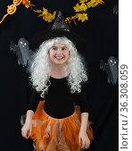 Веселая девочка в белом парике и черно-оранжевом костюме ведьмы на черном фоне с приведениями и оранжевыми тыквами. Стоковое фото, фотограф Наталья Гармашева / Фотобанк Лори