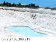 Pamukkale, Turkey - May 11, 2021: One of the most famous attractions of Turkey, Pamukkale is a Unesco World Heritage site. Here in particular the white travertine terraces. Редакционное фото, фотограф Григорий Стоякин / Фотобанк Лори
