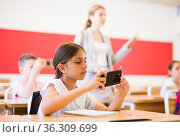 Concentrated tween girl using mobile phone at lesson in class. Стоковое фото, фотограф Яков Филимонов / Фотобанк Лори