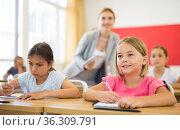 Two positive small school girls sitting together in classroom. Стоковое фото, фотограф Яков Филимонов / Фотобанк Лори