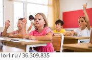 Diligent preteen schoolgirl raising hand to answer at lesson. Стоковое фото, фотограф Яков Филимонов / Фотобанк Лори