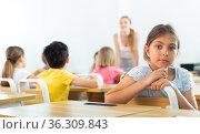 Positive tween schoolgirl sitting at school desk at lesson in class. Стоковое фото, фотограф Яков Филимонов / Фотобанк Лори