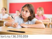Schoolgirl sitting in classroom during lesson in elementary school. Стоковое фото, фотограф Яков Филимонов / Фотобанк Лори