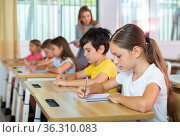 Concentrated tween girl listening to schoolteacher and writing in notebook. Стоковое фото, фотограф Яков Филимонов / Фотобанк Лори