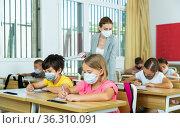 Preteen pupils in protective masks studying in classroom with female teacher. Стоковое фото, фотограф Яков Филимонов / Фотобанк Лори