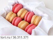 Macaroni cakes with vanilla and strawberry filling in a box close-up. Стоковое фото, фотограф Анна Гучек / Фотобанк Лори