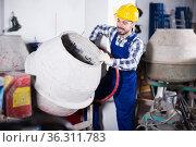 Smiling man using concrete mixer for construction. Стоковое фото, фотограф Яков Филимонов / Фотобанк Лори