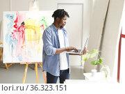 African american male painter at work using laptop in art studio. Стоковое фото, агентство Wavebreak Media / Фотобанк Лори