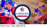 Image of happy labour day text with american flags, star and flag elements, over wood. Стоковое фото, агентство Wavebreak Media / Фотобанк Лори