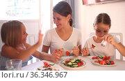 Portrait of woman and two girls eating healthy vegetable salad in room. Стоковое видео, видеограф Яков Филимонов / Фотобанк Лори