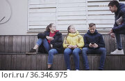 Teen male and female students sitting together outdoor ignoring each other while browsing internet on smartphones. Стоковое видео, видеограф Яков Филимонов / Фотобанк Лори