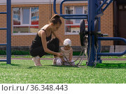 Mom and toddler daughter are walking on the sports ground near the house, the baby is interested in a exercise machine. Стоковое фото, фотограф Евгений Харитонов / Фотобанк Лори