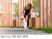 Mom and toddler daughter walk in the city courtyard, child learns to walk. Стоковое фото, фотограф Евгений Харитонов / Фотобанк Лори