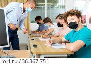 Pupils in masks sitting in class and listening. Стоковое фото, фотограф Яков Филимонов / Фотобанк Лори