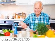 senor man preparing fresh vegetable salad at home in the kitchen. Стоковое фото, фотограф Татьяна Яцевич / Фотобанк Лори