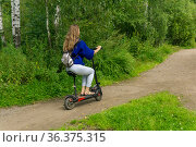 Young woman rides an electric scooter along the path in the park. Стоковое фото, фотограф Евгений Харитонов / Фотобанк Лори