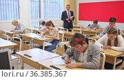 Focused teenage students studying in classroom with teacher, writing lectures in workbooks. Стоковое видео, видеограф Яков Филимонов / Фотобанк Лори