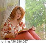 Портрет женщины с книгой в руках, сидящей на подоконнике. Стоковое фото, фотограф Ирина Борсученко / Фотобанк Лори