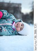 Happy and smiling little child lying on snow and looking at camera, winter season with slippery surface. Стоковое фото, фотограф Кекяляйнен Андрей / Фотобанк Лори