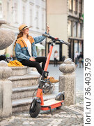 Young woman, sitting on staircase of old historical building in city center, taking picture with her phone. Female traveler exploring Ljubljana's old town on electric scooter. Summer leisure. Стоковое фото, фотограф Matej Kastelic / Фотобанк Лори