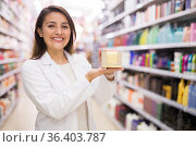 Cheerful saleswoman offering hair care products in cosmetic shop. Стоковое фото, фотограф Татьяна Яцевич / Фотобанк Лори