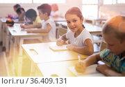 Tween schoolgirl looking at camera with smile in classroom. Стоковое фото, фотограф Яков Филимонов / Фотобанк Лори