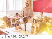 Female teacher working with tweenager pupils in classroom. Стоковое фото, фотограф Яков Филимонов / Фотобанк Лори
