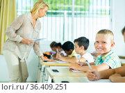 Cheerful blond tween schoolboy in classroom during lesson. Стоковое фото, фотограф Яков Филимонов / Фотобанк Лори