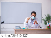 Young male chemist teacher sitting in the classroom. Стоковое фото, фотограф Elnur / Фотобанк Лори