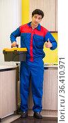 Plumber repairing tap at kitchen. Стоковое фото, фотограф Elnur / Фотобанк Лори