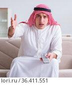 Arab man watching sport football at tv. Стоковое фото, фотограф Elnur / Фотобанк Лори