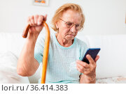 Elderly woman with glasses and cane using a mobile phone. Стоковое фото, фотограф Zoonar.com/Tomas Anderson / easy Fotostock / Фотобанк Лори