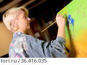 Happy woman paints on canvas using thin brush. Canvas stands on the... Стоковое фото, фотограф Zoonar.com/DAVID HERRAEZ CALZADA / easy Fotostock / Фотобанк Лори