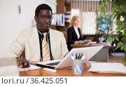 Focused african american businessman works in the office at an computer. Стоковое фото, фотограф Яков Филимонов / Фотобанк Лори