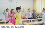 Smiling tweenager pupils doing little warm-up in class with female teacher at lesson in elementary school. Стоковое видео, видеограф Яков Филимонов / Фотобанк Лори