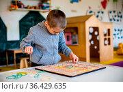 Lovely preschool boy exploring geoboard at daycare. Montessori games... Стоковое фото, фотограф Zoonar.com/OKSANA SHUFRYCH / easy Fotostock / Фотобанк Лори