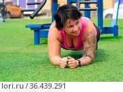 Muscular plump woman exercising on the sports ground. Стоковое фото, фотограф Евгений Харитонов / Фотобанк Лори