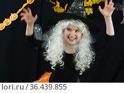 Веселая девочка в белом парике и  костюме ведьмы на черном фоне. Стоковое фото, фотограф Наталья Гармашева / Фотобанк Лори