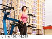 Young woman shakes her biceps using street weight machine. Стоковое фото, фотограф Евгений Харитонов / Фотобанк Лори