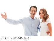 Portrait of happy couple isolated on white background, man pointing... Стоковое фото, фотограф Zoonar.com/Tatiana Badaeva / easy Fotostock / Фотобанк Лори