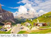 View to Passo Selva di Val Gardena whith Cappella di San Maurizio white chapel, Hotel and parking car with mountains Langkofel in the background. Dolomiti, Trentino Alto Adige, Dolomites alps, Italy. Стоковое фото, фотограф Алексей Ширманов / Фотобанк Лори
