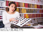 Interested Latina looking at palette of hair colors in cosmetics store. Стоковое фото, фотограф Татьяна Яцевич / Фотобанк Лори