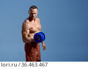 Male athlete with dumbbells poses in studio. Стоковое фото, фотограф Tryapitsyn Sergiy / Фотобанк Лори