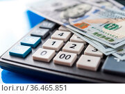 Business and financial background with dollars and calculator. Economy... Стоковое фото, фотограф Zoonar.com/BASHTA / easy Fotostock / Фотобанк Лори