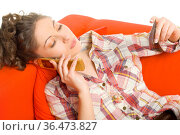 Young, beautiful woman lying on orange couch. Talking on mobile phone... Стоковое фото, фотограф Zoonar.com/Tomasz Trojanowski / easy Fotostock / Фотобанк Лори
