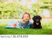 Cute preschool girl play with pets on fresh green lawn at the garden... Стоковое фото, фотограф Zoonar.com/OKSANA SHUFRYCH / easy Fotostock / Фотобанк Лори