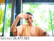 Headshot of indian woman sit on potdoor cafe waving hand looks to... Стоковое фото, фотограф Zoonar.com/Max / easy Fotostock / Фотобанк Лори