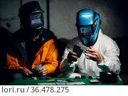 Two welders in welding masks play poker. Стоковое фото, фотограф Zoonar.com/Max / easy Fotostock / Фотобанк Лори