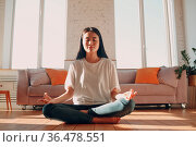 Asian woman doing yoga and zen like meditation lotus pose in casual... Стоковое фото, фотограф Zoonar.com/Max / easy Fotostock / Фотобанк Лори