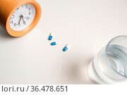 Alarm clock and white blue pills on white table background. Стоковое фото, фотограф Zoonar.com/Max / easy Fotostock / Фотобанк Лори